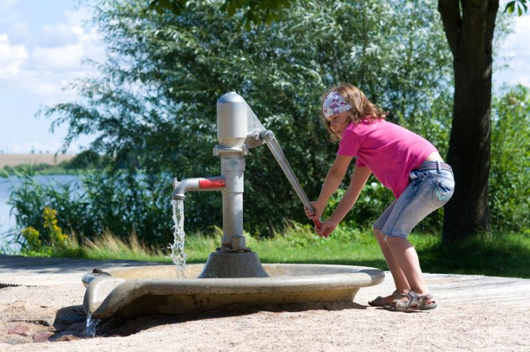 child at the water pump