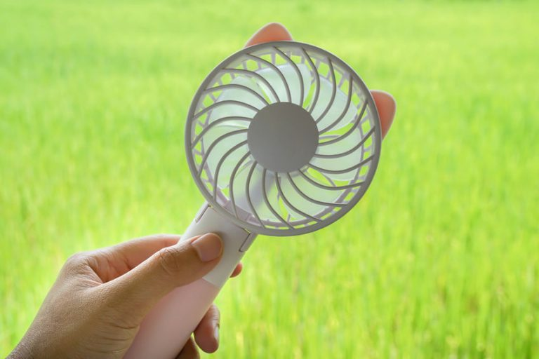 close up woman hold portable motor USB fan for outdoors travel