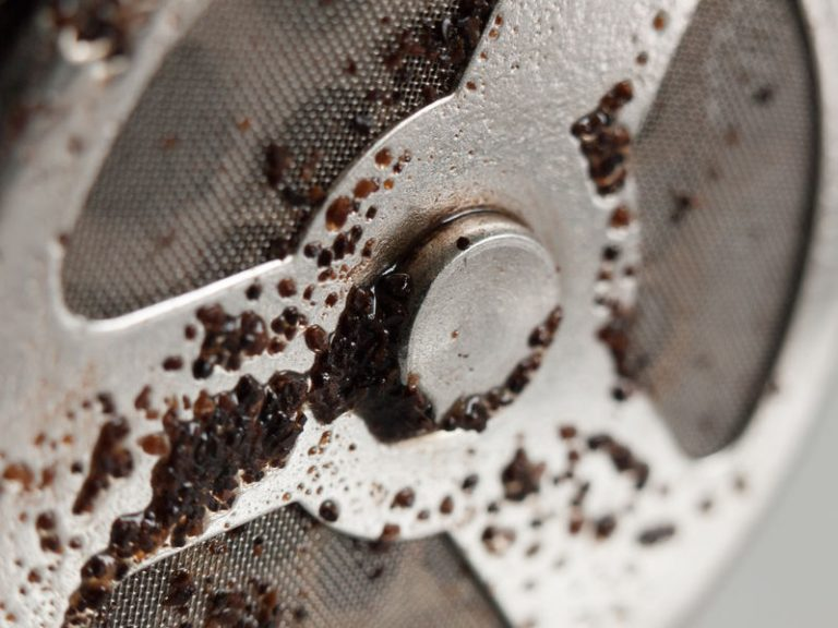 a used coffee strainer close up with wet coffee grains stuck to it