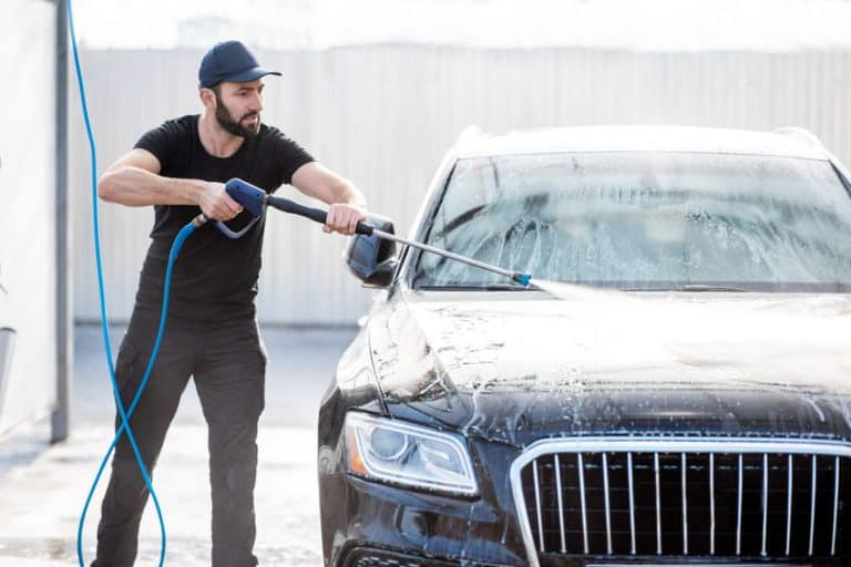 Man washing car with water gun